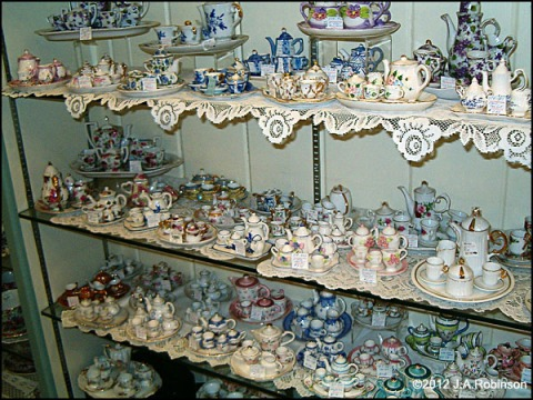 Phot: Several shelves in a china shop are filled with dozens of miniature tea sets.  The shelves are lined with lace.