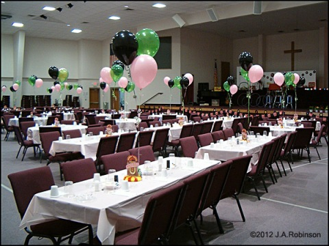 A hall full of festively decorated tables has clusters of helium baloons floating above each table.