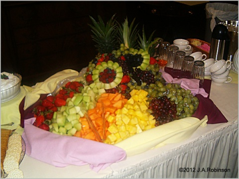 "An elaborate fruit display with linen ""bumpers"" around the edges is seen at a wedding reception ."