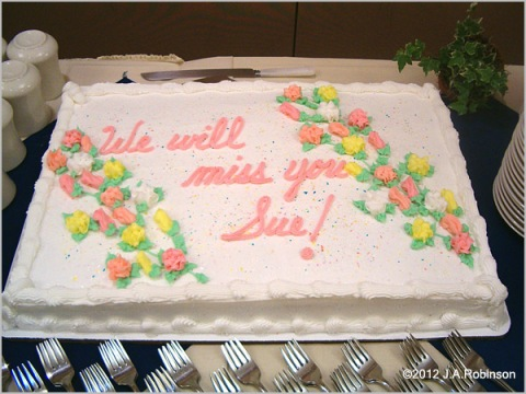 """A beautiful retirement cake has the words, """"We will miss you Sue!"""""""