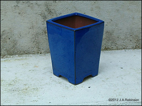 Photo of a tall, square blue flower pot.