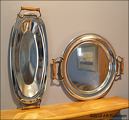 Photo of two shiny metal trays with handles sitting on end on a a shelf--one round and one oval